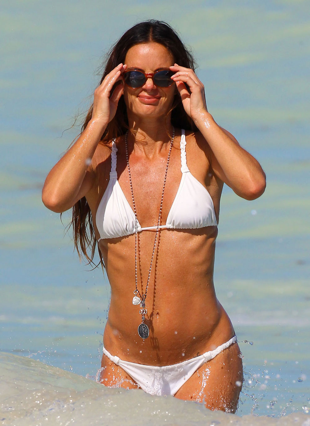 With her slim body and Light brown hairtype without bra (cup size 34B) on the beach in bikini