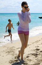 ANNE HATHAWAY in a Covered Bikini on the Beach in Miami