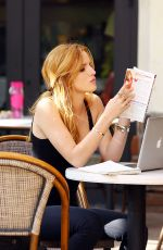 BELLA THORNE Reading a Book at a Cafe in Los Angeles
