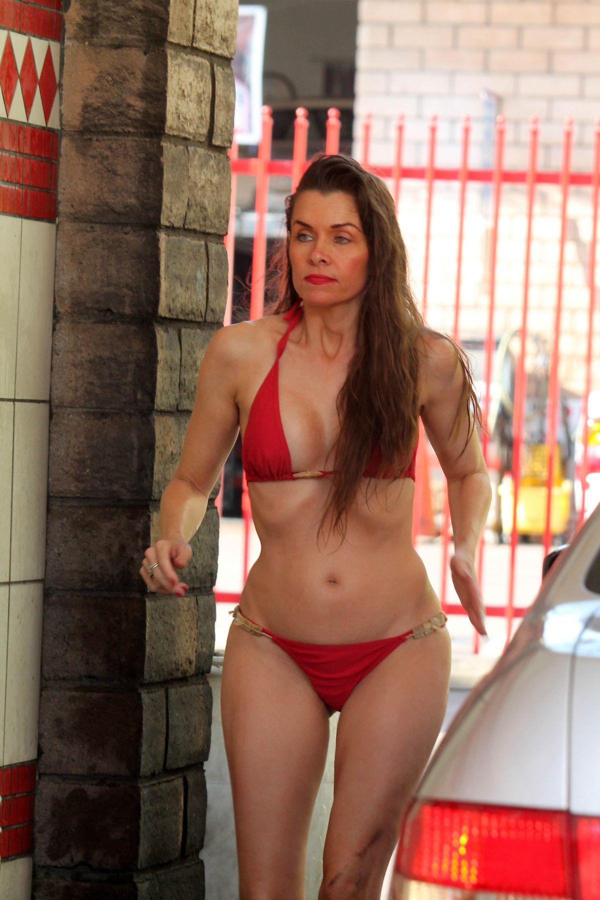 Alicia Arden in a bikini on a city street