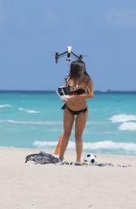 CLAUDIA ROMANI in Bikini Playing with a Dron on the Beach in Miami