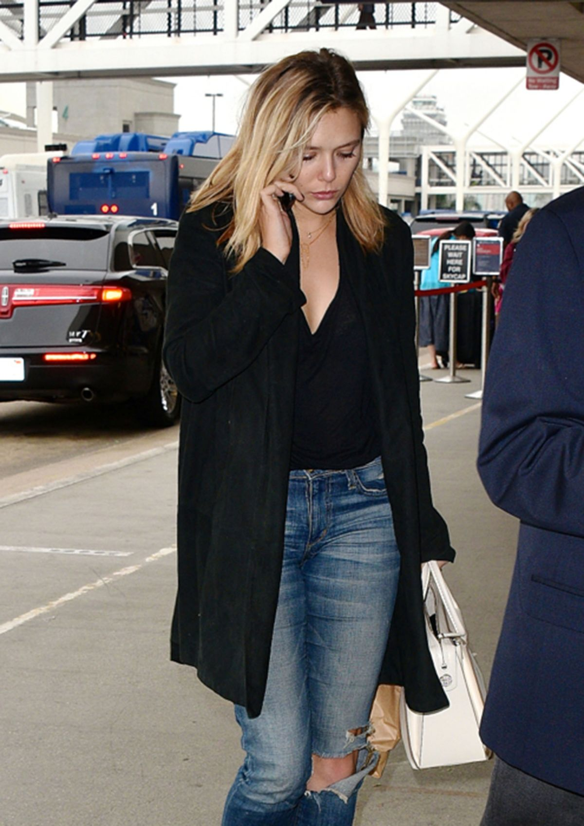 ELIZABETH OLSEN in Ripped Jeans at LAX Airport in Los Angeles 10/16/2015