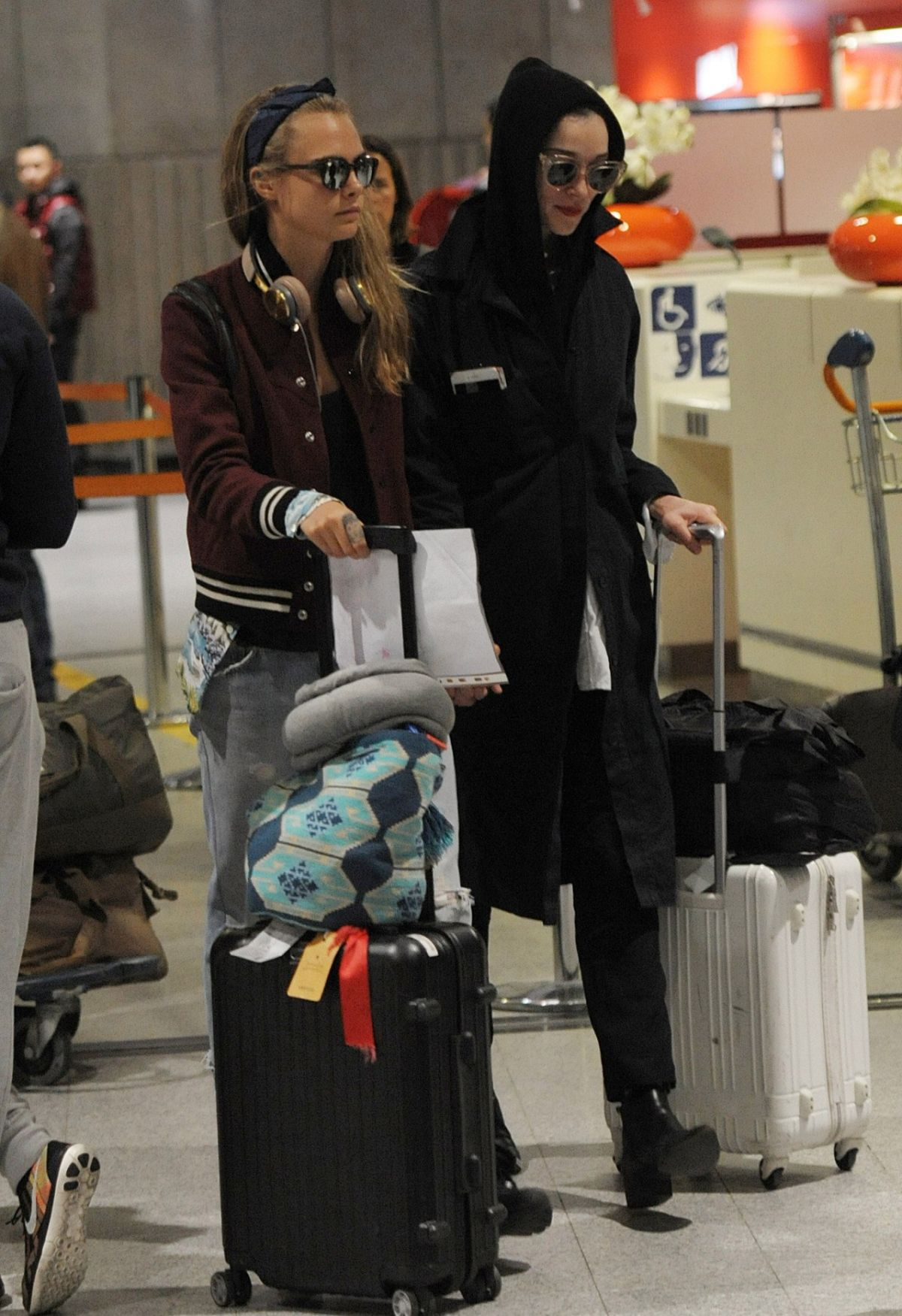 CARA DELEVINGNE and ANNIE CLARK at Charles-De-Gaulle Airport in Paris 02/28/2016