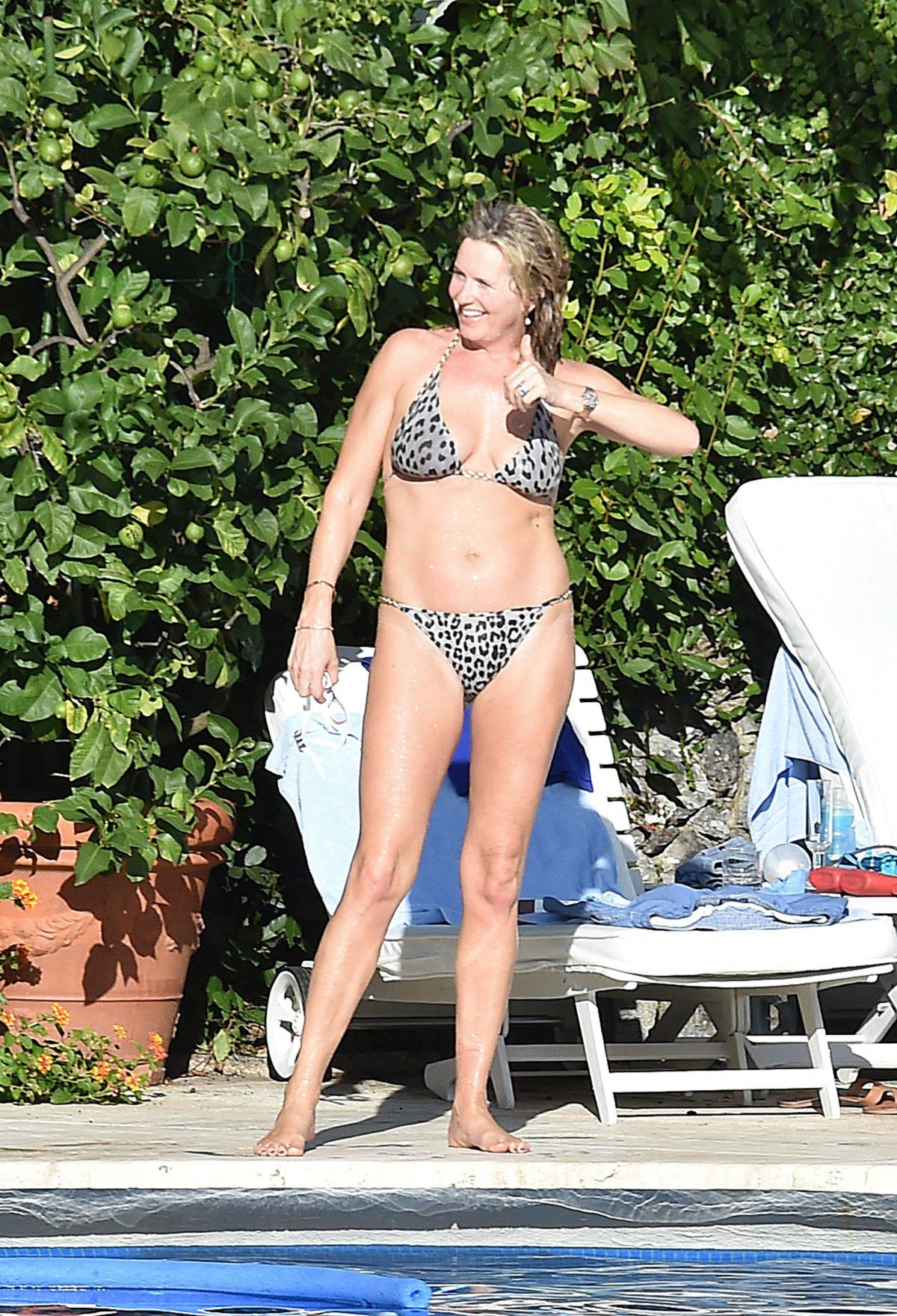 PENNY LANCASTER in Bikini at a Pool in Italy 09/19/2016