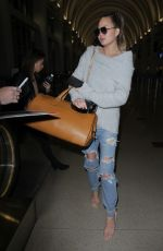 CHRISSY TEIGEN in Ripped Jeans at LAX Airport in Los Angeles 04/13/2017