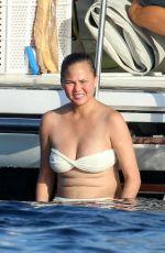 CHRISSY TEIGEN in Bikini at a Boat in Sardinia 08/30/2017