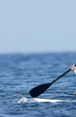 CHRISSY TEIGEN Paddleboarding in Sardinia 08/30/2017