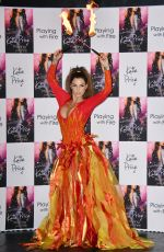 KATIE PRICE Fire Breathing at Her New Book Playing with Fire Photocall in London 01/17/2017