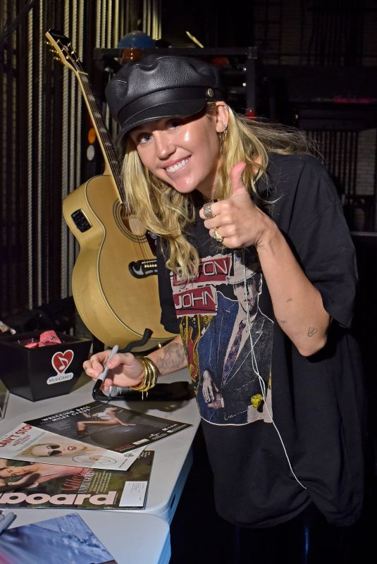 MILEY CYRUS Signs a Guitar and Microphone at Madison Square Garden in New York for Grammys 2018 Charities 01/25/2018
