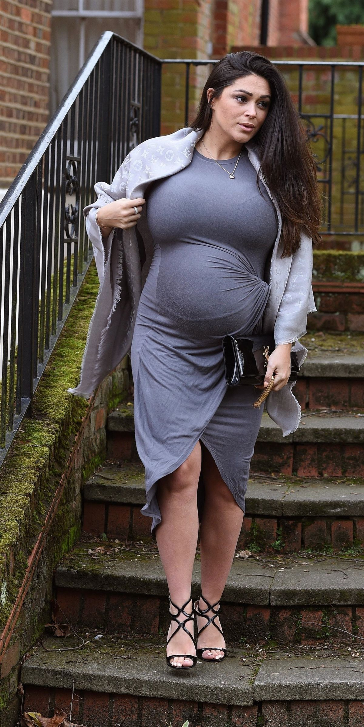 pregnant woman holds her tummy and looks at it - WorkLife Law