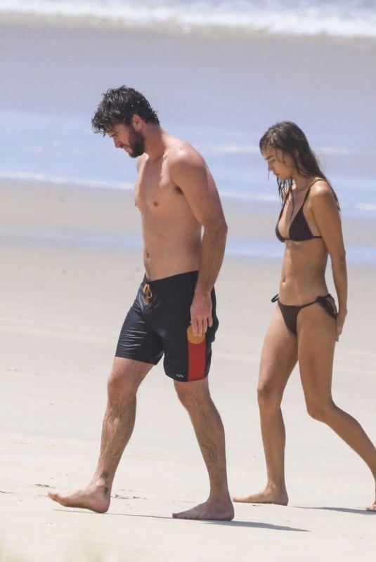 GABRIELLA BROOKS in Bikini and Liam Hemsworth at a Beach in Byron Bay 02/24/2021
